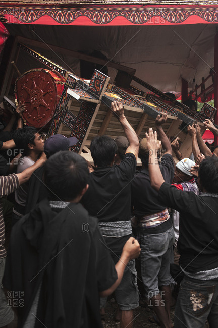 Rantepao, Sulawesi, Indonesia - September 3, 2013: Family lifting coffin in the air in celebration at a Toraja funeral