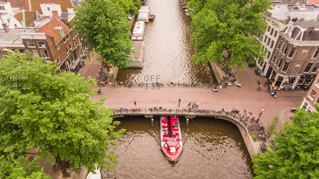AMSTERDAM, THE NETHERLANDS - 7 July 2016 : Aerial view of a barge passing under a bridge on the canal in Amsterdam, The Netherlands.