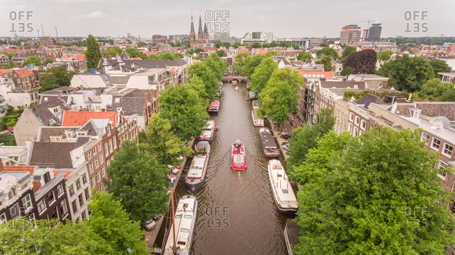 Aerial view of a barge driving in the canal of Amsterdam, The Netherlands.