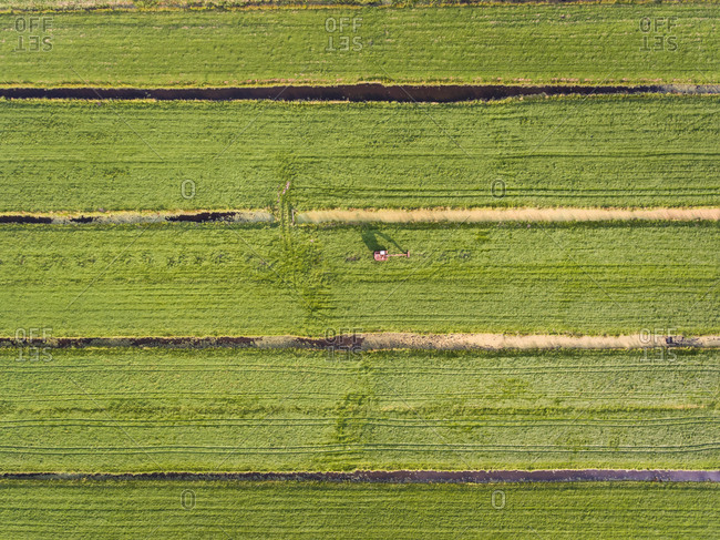 Aerial. view of a tractor working in the fields in The Netherlands.