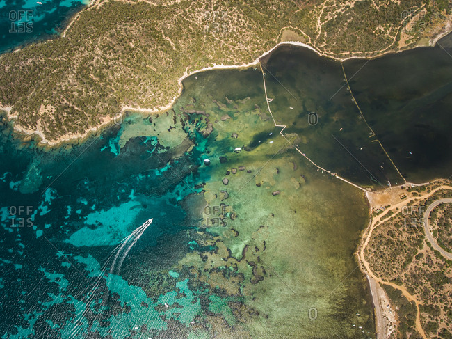 Aerial view of a boat navigating close to Sardinia coast, italy.
