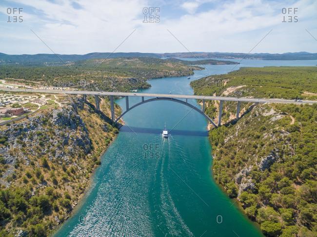 Motorway bridge over Krka river with boat sailing beneath, Croatia