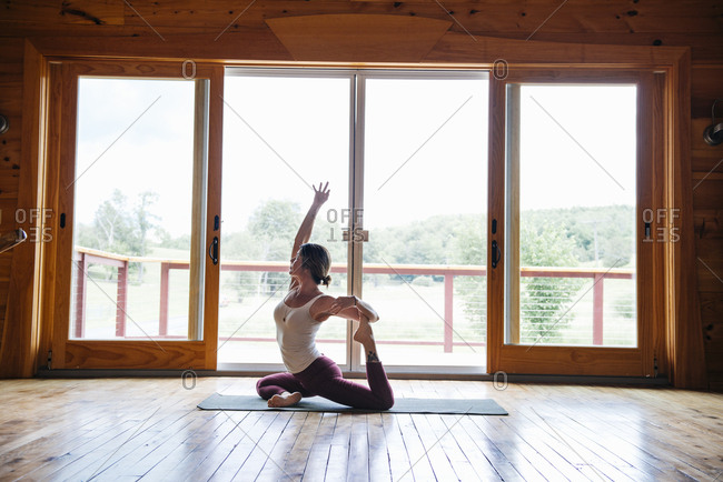 Woman practicing yoga while sitting on hardwood floor by glass door in loft