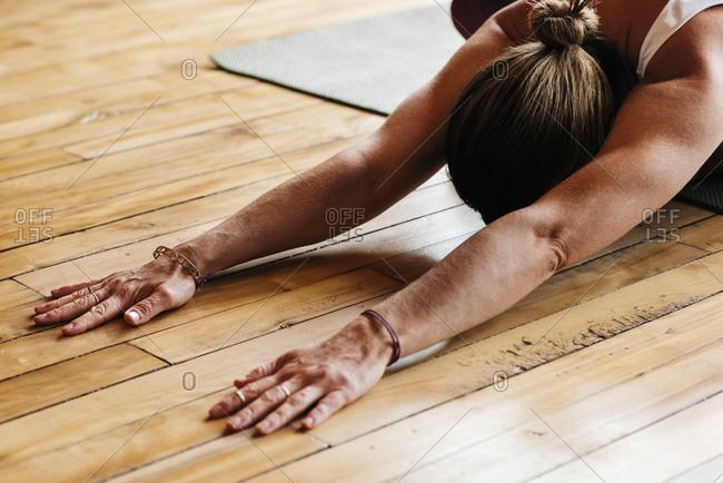 Woman exercising on hardwood floor in house