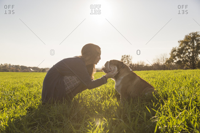Woman playing with English Bulldog on grass