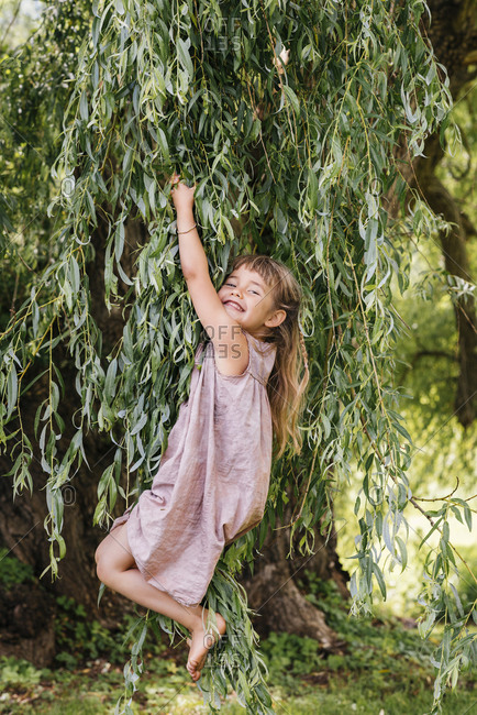 Playful girl hanging from tree branches at park