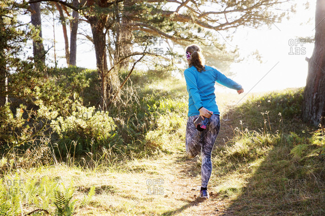 Woman stretching on forest path at Sandhammeren, Sweden