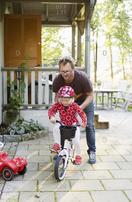 Man teaching his daughter to ride bicycle in Sweden