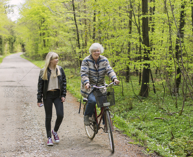 Grandmother and granddaughter with bicycle on forest road