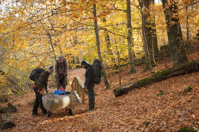 Men carrying kayak through forest in Blekinge, Sweden