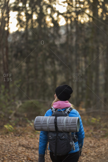 Rear view of woman hiking through forest in Lerum, Sweden