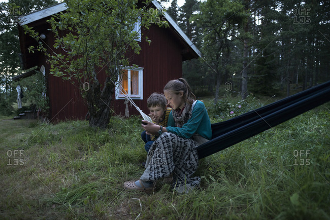 A boy and a girl in a hammock looking at a cell phone
