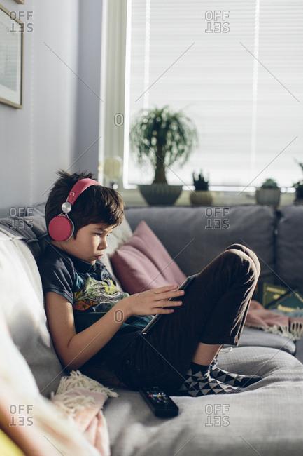 Boy with headphones sitting on sofa