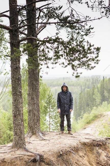 Man standing under trees