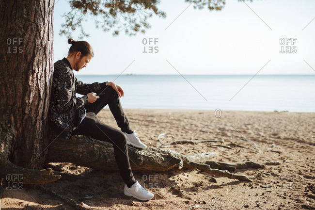 A young man outdoors looking at his cell phone