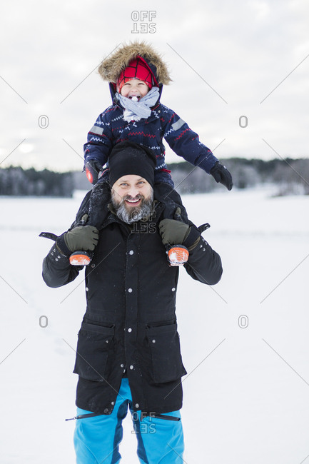 Son of fathers shoulders in snow