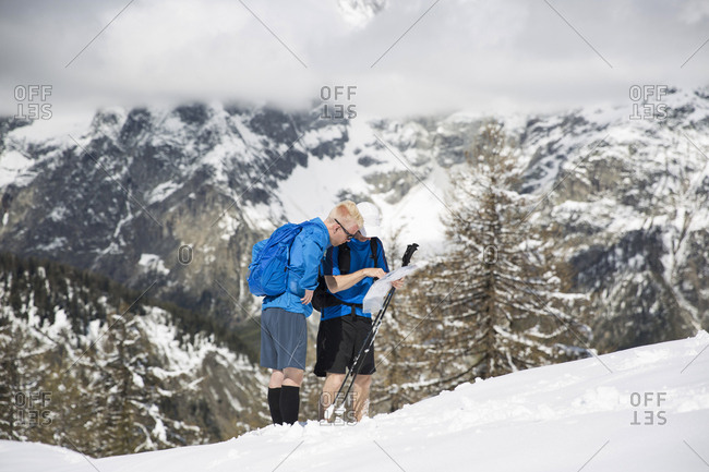 Men looking at a map during a hike up a mountain in Courmayeur, Italy