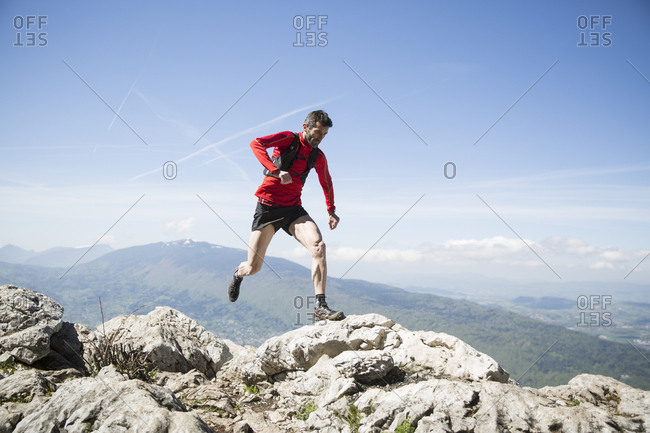 Man running on rocks in Annecy, France