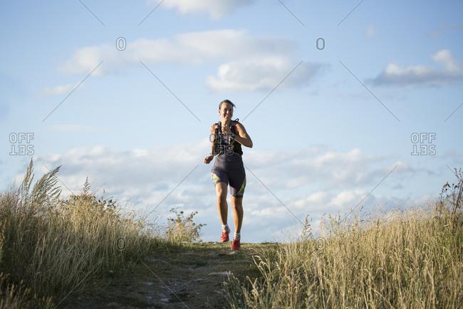 Woman jogging through field in Akersberga, Sweden