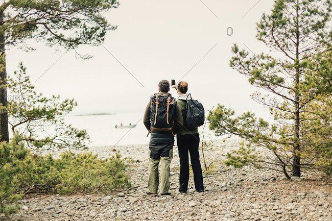 Rear view of hiking couple with smart phone in Sodermanland, Sweden