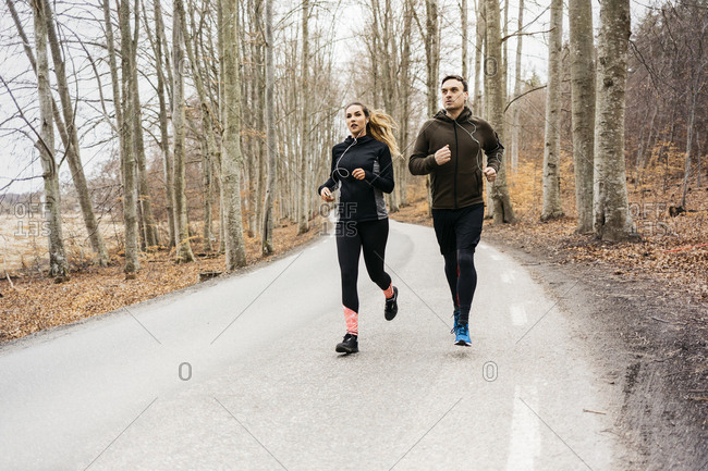 Man and woman running along rural road in Sodermanland, Sweden