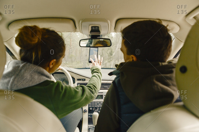 Couple in car getting directions on smart phone in Sodermanland, Sweden