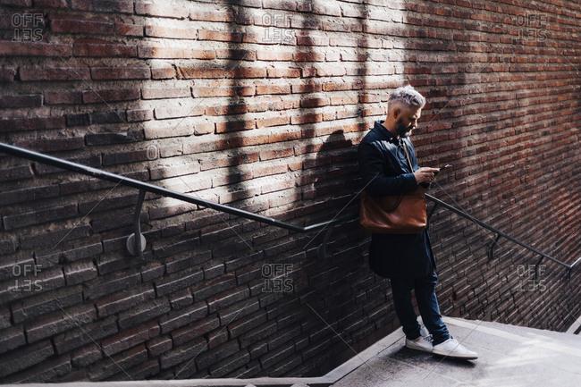 Man beside brick wall on smart phone in Sweden