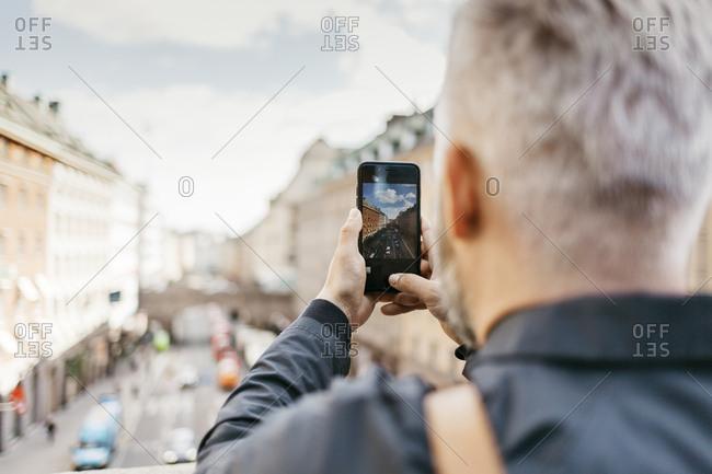 Man taking photograph of street in Stockholm, Sweden