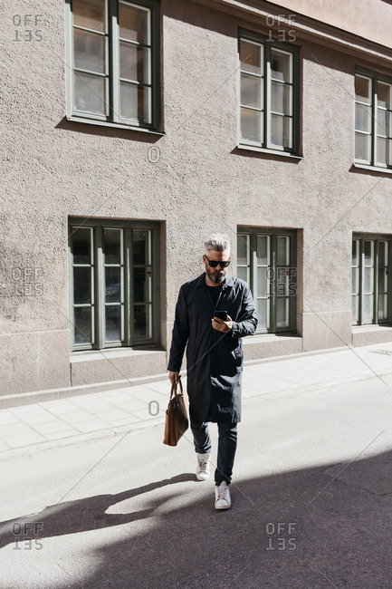 Man walking down street with smart phone in Stockholm, Sweden