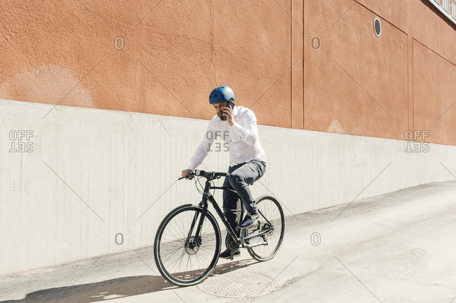 Man on smart phone while bicycling in Sweden