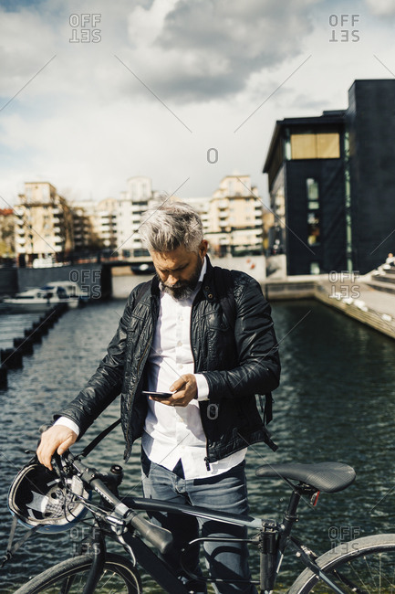 Man on smart phone with bicycle in Stockholm, Sweden