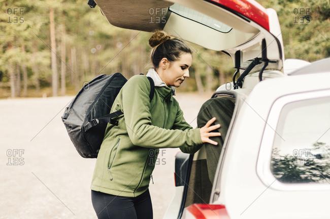 Woman loading bags in car in Sodermanland, Sweden