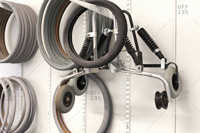 Rubber tires for wheelchairs and other parts hanging on wall