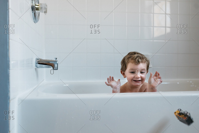 Little boy gleefully throwing toy out of the bath tub
