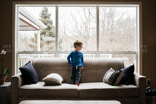 Young boy standing on couch with back to the window