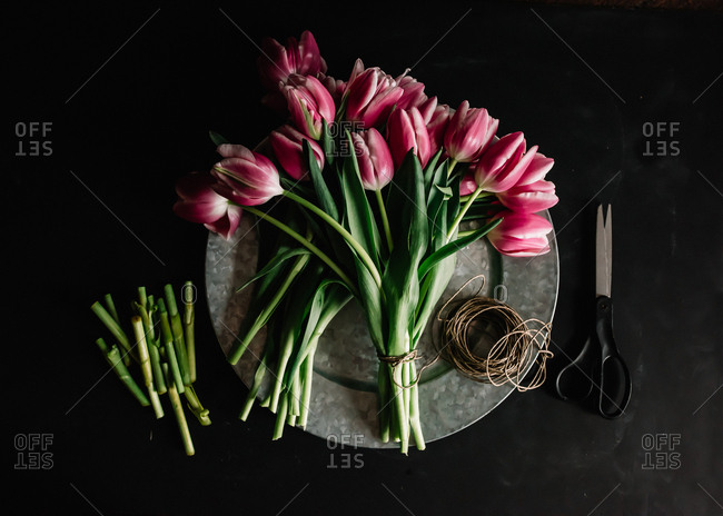 Bouquet of tulips laid out on platter with scissors and twine