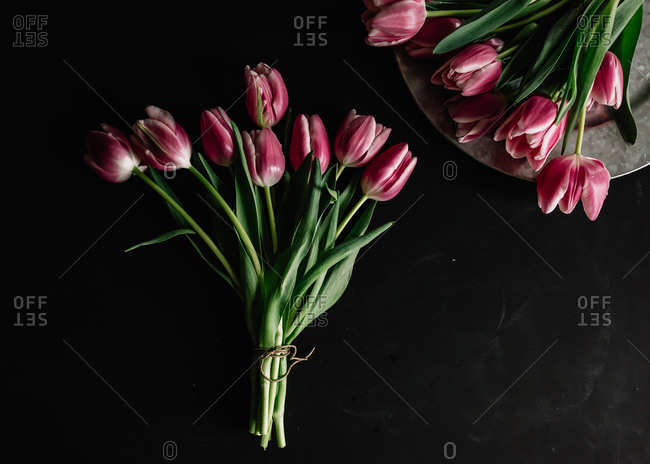 Bunch of tulips made into bouquet with second bunch laid out on platter