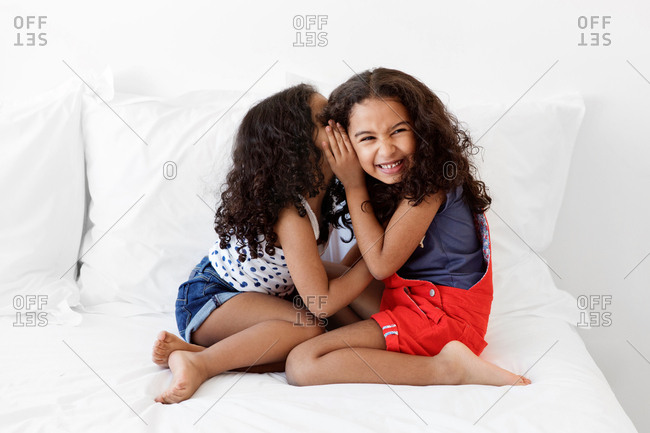 Young girl sitting on bed whispering in sister's ear