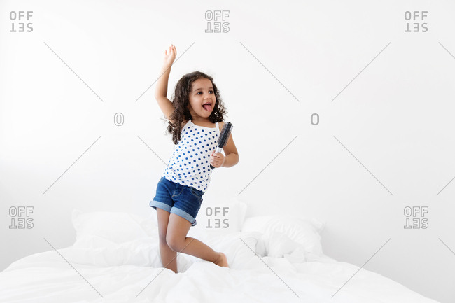 Little girl standing on bed and pretending to be a pop star