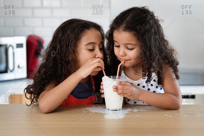 Little girls sharing a glass of milk at the kitchen counter