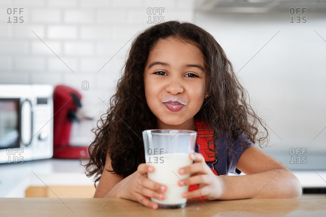 Little girl with a milk mustache from drinking glass of milk