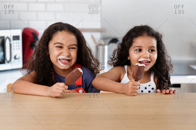 Little girls eating ice cream bars with ice cream all around their mouths