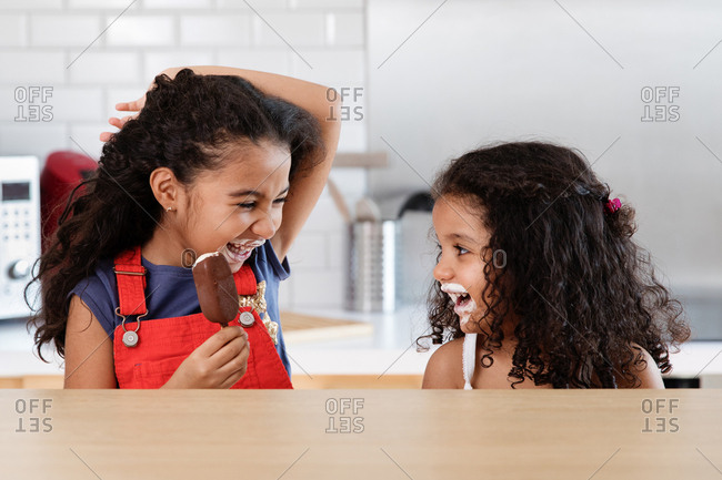 Little girls making each other laugh while eating ice cream bars