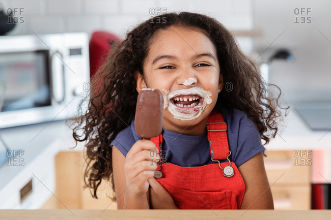 Little girl laughing with ice cream all over mouth and nose while eating ice cream bar