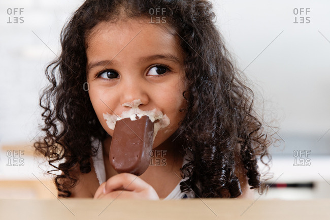 Little girl quietly enjoying her ice cream bar with ice cream all over mouth and nose