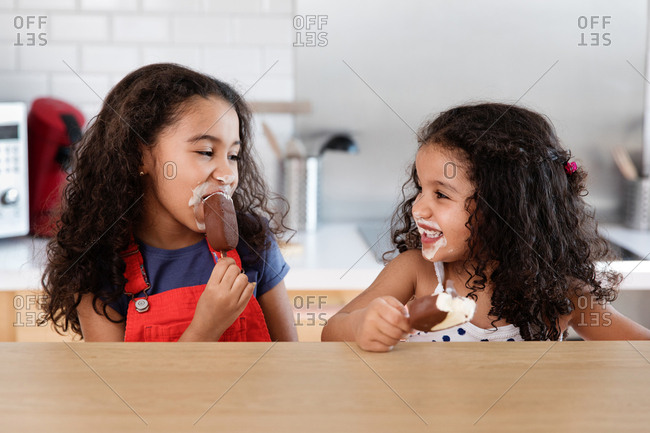 Little girls looking at each other as they messily eat ice cream bars