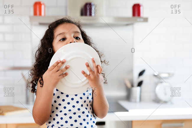 Little girl licks last remaining drops from plate