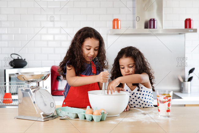 Young girls mixing ingredients for a cake together