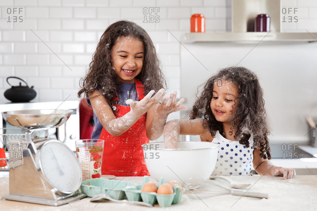 Little girls getting up to mischief in the kitchen while preparing a cake