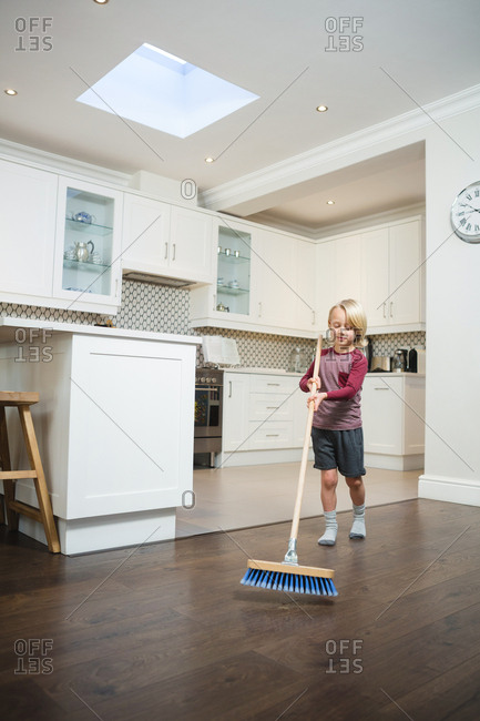 Boy cleaning floor with broom in kitchen at home